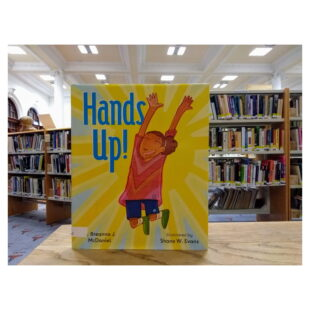 """a yellow book cover with the words """"Hands up!"""" written in blue next to an illustration of a child jumping up sits in the library in front of bookshelves"""