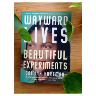 """the book cover for """"Wayward Lives Beautiful Experiments"""" sits on a table"""