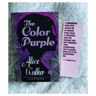 """A purple and black book cover for the """"The Color Purple"""" sits on a sheet"""