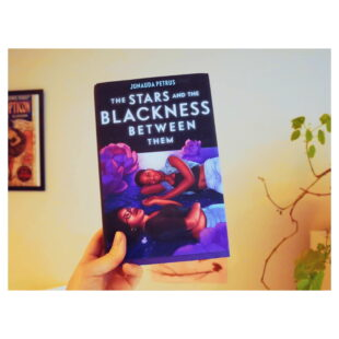 """the book cover for """"The Stars and the Blackness Between Them"""" is held up in front of a white wall"""