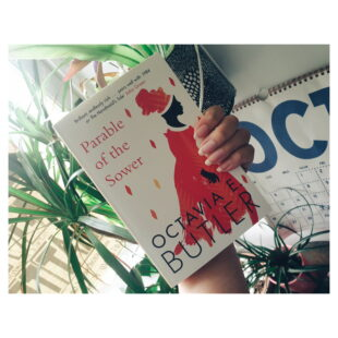 a hand hold up a book in front of a window filled with plants. the book is Parable of the Sower by Octavia E Butler. The cover is white with an illustration of a woman in a red rover and head scarf.