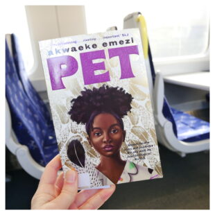 """a hand holds a book """"PET"""" os written in large purple letters above the picture of a young black woman"""