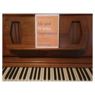 """the book """"Me and White Supremacy"""" sits on a piano"""