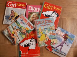 A selection of girls' annuals from the GWL Collection, on a wooden table. The annuals are from the 1950s, 60s and 70s, and have illustrations or photos of girls, some doing activities or sports. All the girls are white.