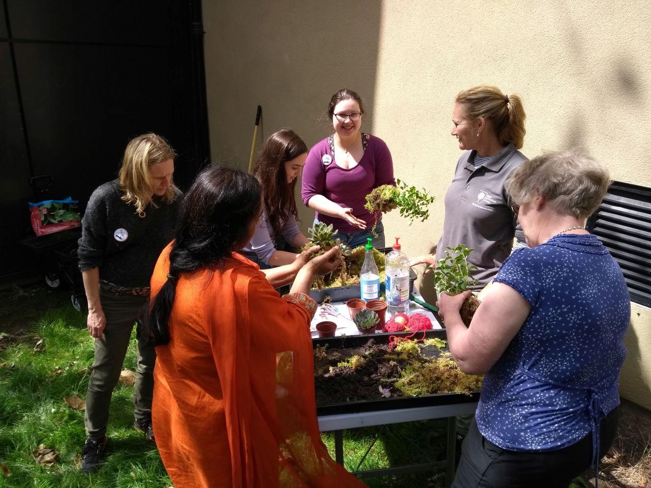 Women from GWL plant a garden outside GWL's building