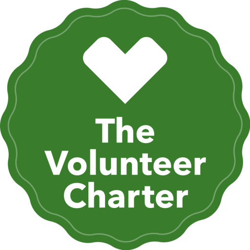 "The Volunteer Charter logo. A green badge with the words ""the volunteer charter"" in white."