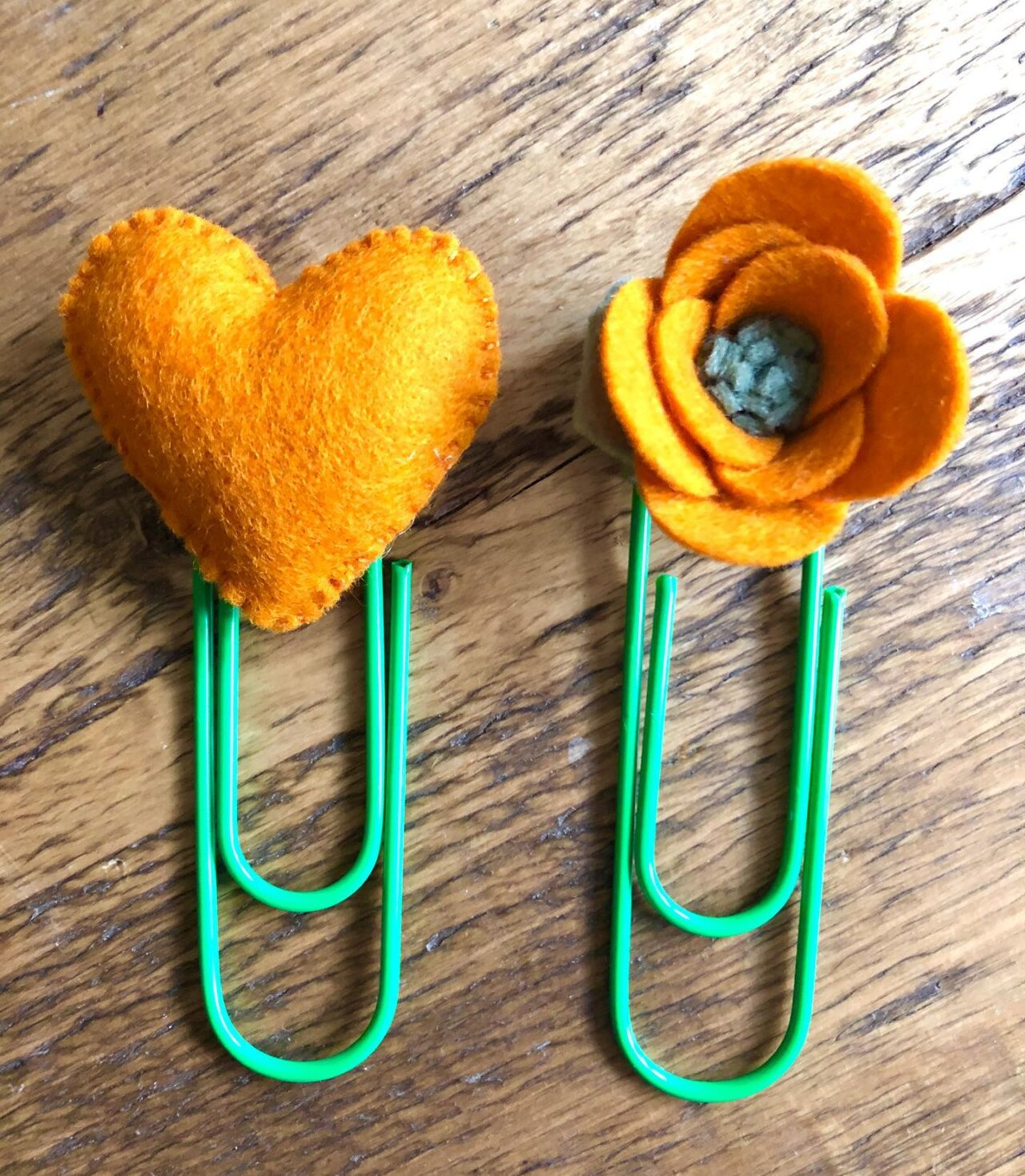 A yellow felt heart and a yellow felt flower have been added to two paperclips. Craft created by Purple Bee.
