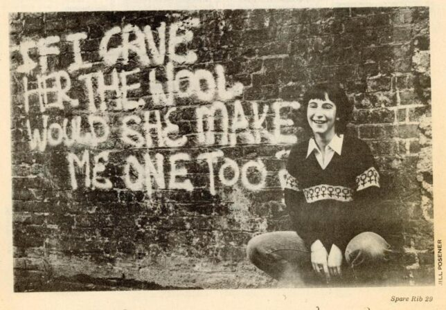 Monochrome photograph of a woman wearing the Spare Rib 'woman's woolly' knitted jumper, squatting beside a wall sprayed with the words 'If I gave her the wool would she make me one too?'