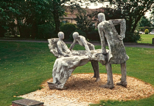 a metal sculpture by Edith Simon showing three figures, two of whom are standing, the third is lying in a bed which appears to levitate