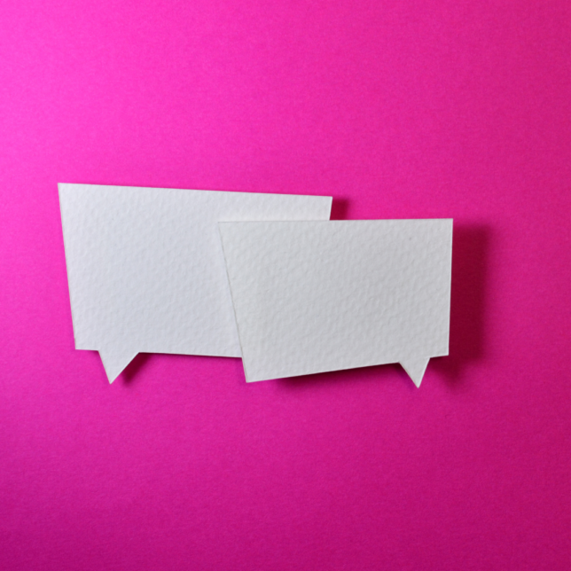 two papercut outs of speech bubbles sit on top of a shocking pink background