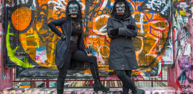 Two figures are photographed standing against a wall which is daubed with colourful graffiti. The figures are dressed in dark clothing and each is wearing a fancy dress style gorilla mask