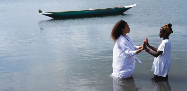 Alberta Whittle, Still from Holding the Line, 2020. Two women of colour stand in deep water, facing each other with their hands pressed together. A small low boat floats in the water behind them.