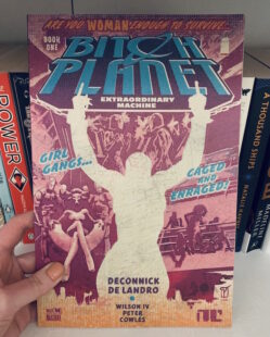 Image shows cover of Bitch Planet. A silhouette of a woman's body is visible and she is giving two fingers. To the right hand side of the silhouette a woman is sitting on a chair with bodyguard type people behind her. To the right hand side women are standing and sitting next to a railing. Picture is taken against the backdrop of a bookcase.