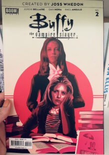 Image shows cover of Buffy the Vampire slayer issue 2. Buffy is sat at a desk with books looking at the reader and Drusilla stands behind her in a pink circle.