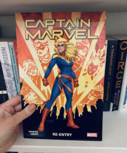 Image shows cover of Captain Marvel standing in a power pose wearing her uniform. Background lights show past depictions of Captain Marvel shining through. Picture is taken against the backdrop of a bookcase.