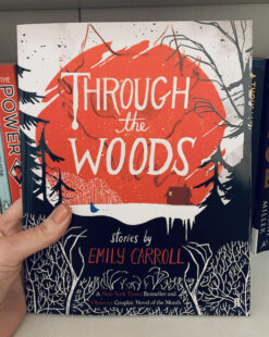 Image shows cover of Through the Woods and depicts a black and white forest with a red background that has 'Through the Woods' and a house within it. Picture is taken against the backdrop of a bookcase.
