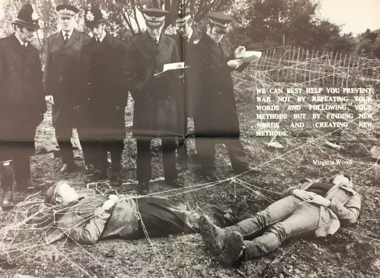 Two women lying down covered in string, forming a web and attached to nearby fences. Standing over them are six policemen, two writing notes. There is a quote from Virginia Woolf which reads: 'We can best help you prevent war not by repeating your words and following your methods but by finding new words and creating new methods'