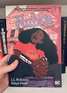 Image shows cover of Nubia sitting looking at the reader. She is wearing a Wonder Woman t-shirt and bracelets of submission. Picture is taken against the backdrop of a bookcase.