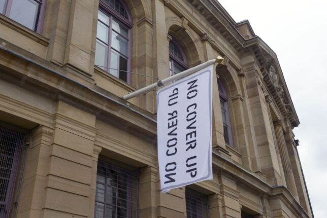 A large white flag with the slogan 'No Cover Up' hanging from the front of the GWL building. Ingrid Pollard, 'No Cover Up', 2021. Photo: Alan Dimmick