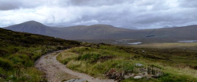 A rough track leading across moorland and into the hills