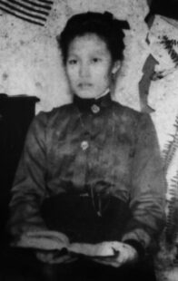 Black and white picture of Kim Ransa. She is sitting down, holding a book. Her hair is up and she is wearing Western clothes.