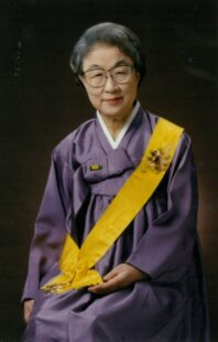 Lee Tai-young sitting down, wearing a purple Hanbok (traditional Korean dress) with a gold sash.