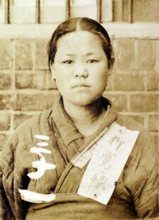 Photo of Yu Gwan-sun. Her hair is up and she is wearing a worn-out hanbok (traditional Korean dress). A piece of paper is attached to it. She is looking straight into the camera.