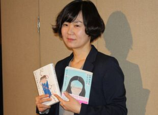 Photo of Cho Nam-joo holding two editions of her book.