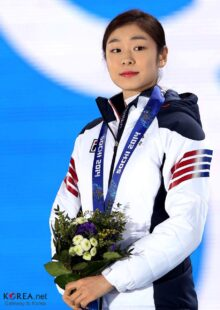 Yuna Kim smiling, wearing her competition outfit and a medal, holding a bouquet.