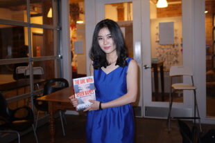 Lee Hyeon-seo in a blue dress holding her book.