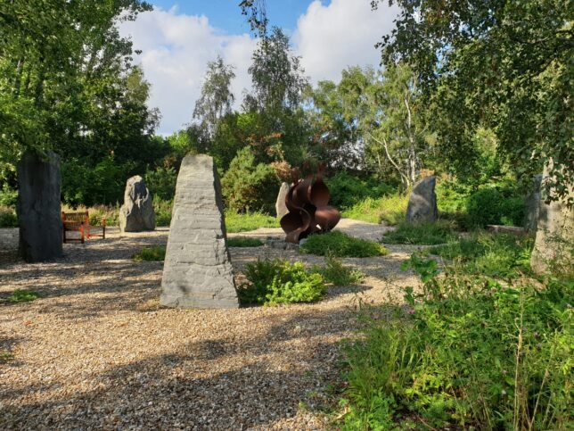 This is a photograph of the Greenham memorial garden. In the center is a large reddish brown metal sculpture of a camp fire flame. It is surrounded by seven big grey standing stones.