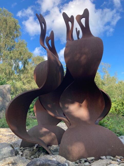 A close up photograph of the flame sculpture in the Greenham memorial garden. It is made of large pieces of reddish brown metal curved to resemble a campfire flame.  There are trees in the background and a blue sky with a couple of clouds.