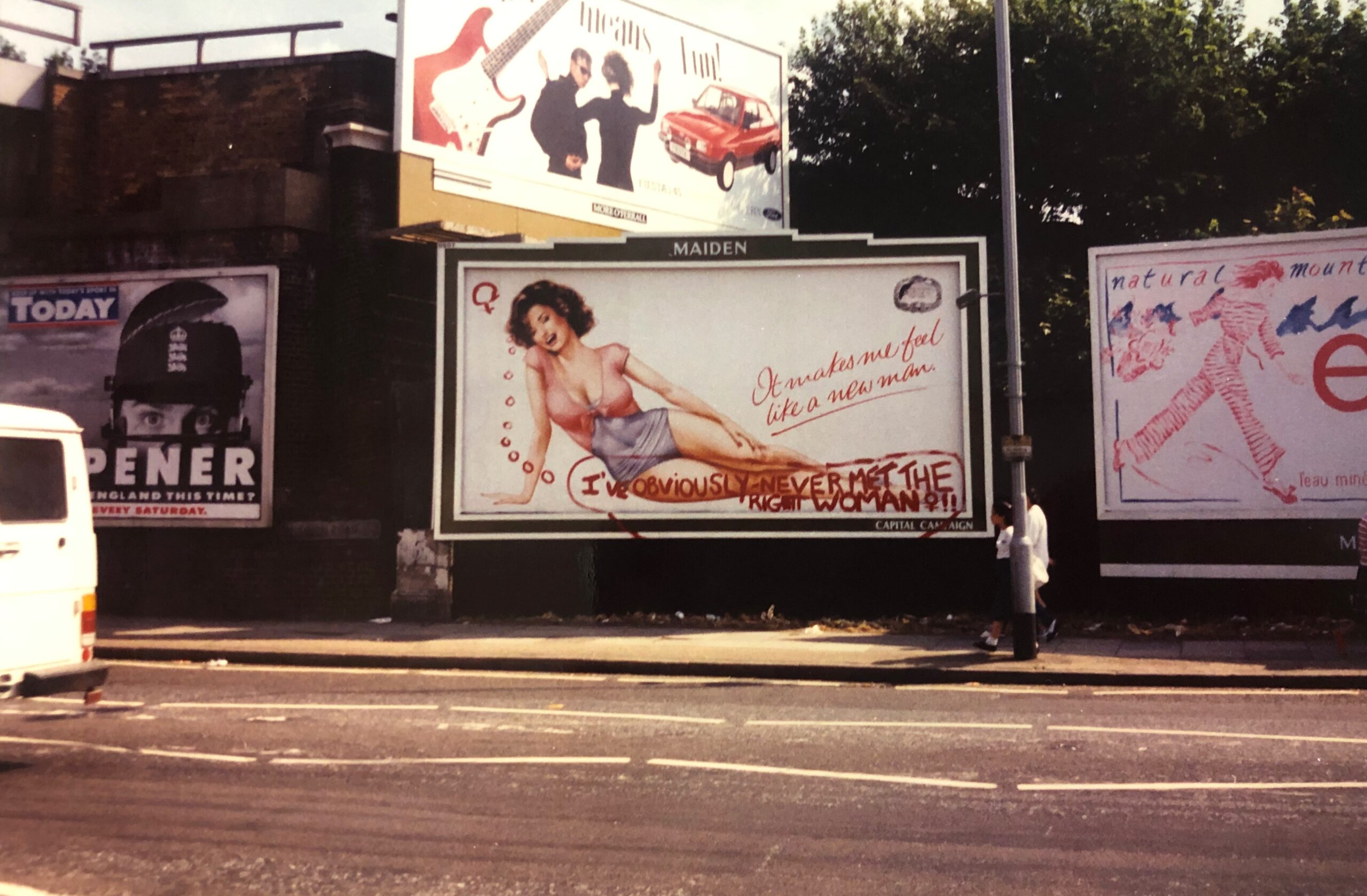 Billboard advert featuring a pin-up-style woman and the caption, 'It makes me feel like a new man!'. Below this, in red paint, a thought bubble: 'I've obviously never met the right woman!!'
