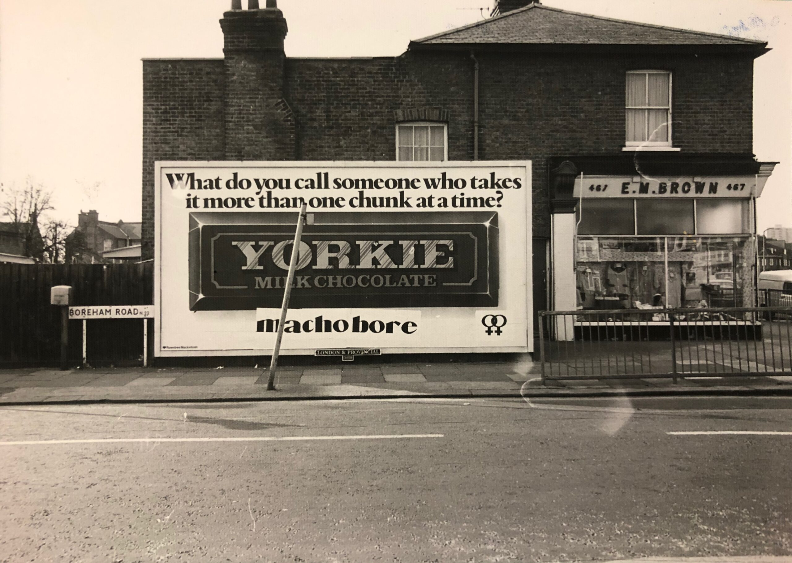 Billboard advert for Yorkie chocolate, featuring a Yorkie bar in the centre and, 'What do you call someone who takes it more than one chunk at a time?' above. Below the bar, someone has wheat-pasted 'macho bore' and the lesbian symbol.