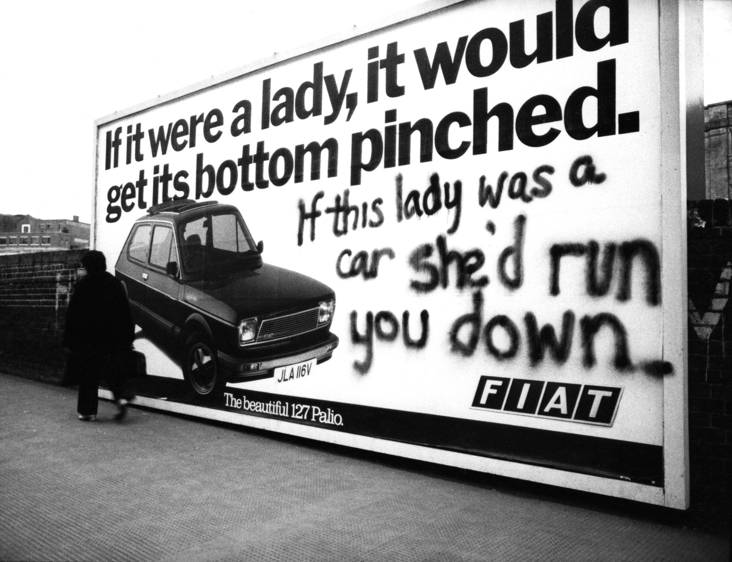 A billboard advert for a Fiat 127 Palio, featuring an image of the car in the bottom left corner and the slogan 'If it were a lady, it would get its bottom pinched.' Beneath this, someone has spray-painted 'If this lady was a car she'd run you down.'