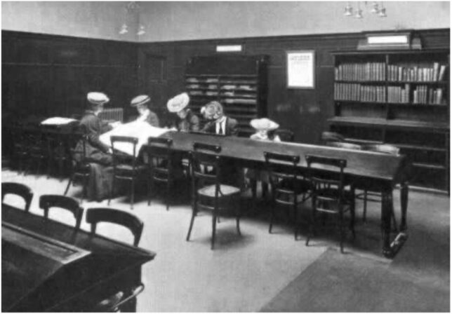 Ladies in the reading room at woodside library, dressed in their fancy clothes and sitting at desks