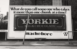 Billboard for Yorkie chocolate, featuring image of the chocolate bar in centre and text above it that reads, 'What do you call someone who takes it one chunk at a time?' Below the bar, someone has wheat-pasted the answer: 'macho bore'.
