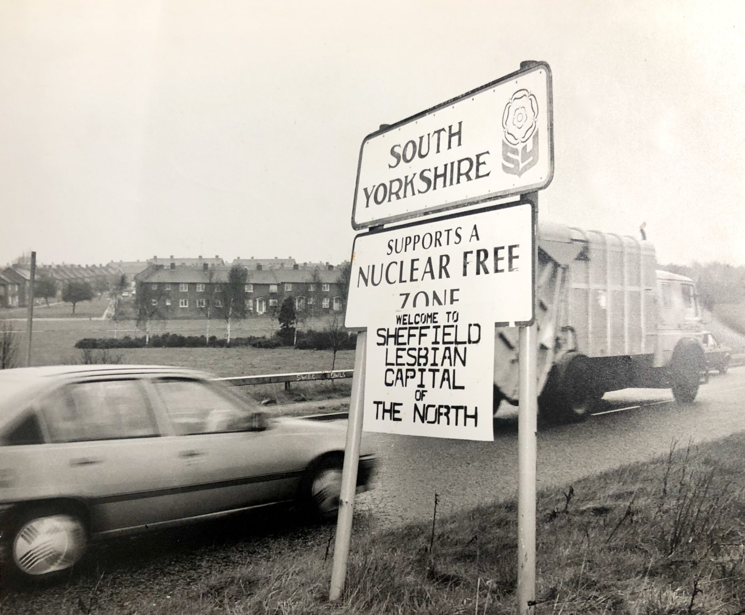 Boundary sign for South Yorkshire, to which someone has affixed a placard that reads 'Welcome to Sheffield lesbian capital of the north'. Houses are visible in the background, while a car drives past in the foreground.
