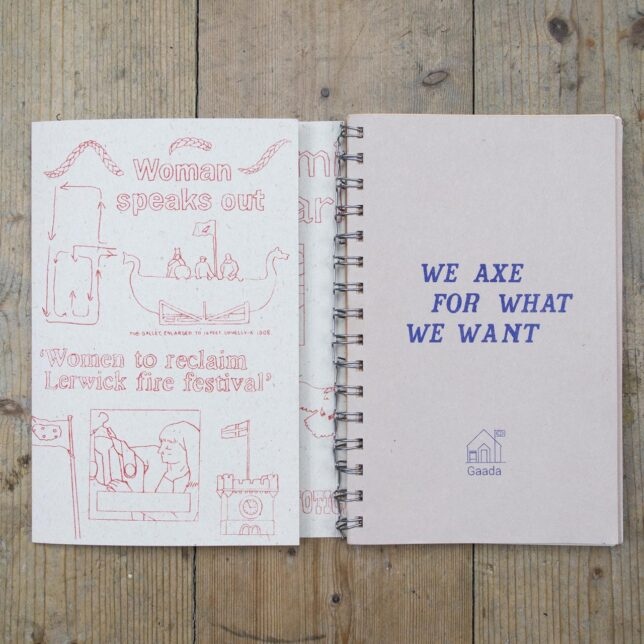 A small sketchbook. On the left hand page there are various illustrations of images related to Shetland such as viking long boats and flags. There is writing that says 'Woman speaks out' and 'Women to reclaim Lerwick fire festivall'. The right hand page has text that reads 'We axe for what we want' in blue letting, with the GAADA symbol underneath - a blue line drawing of the GAADA premises.